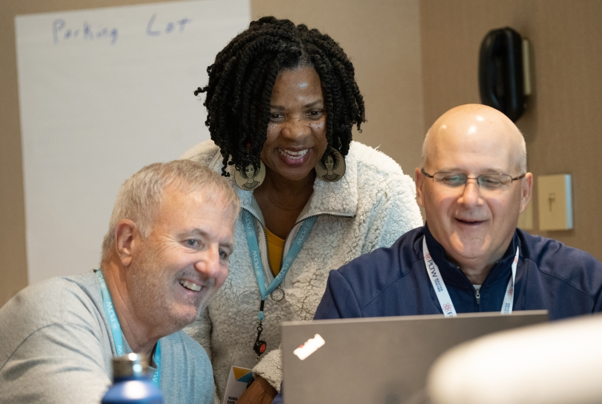 three PLTW Summit Kansas City educators gathered around a laptop